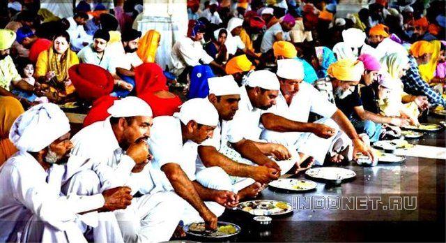 Верующие едят общинную пишу в Золотом храме в Амритсаре